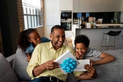 Happy kids surprising their father with a gift for Father's Day