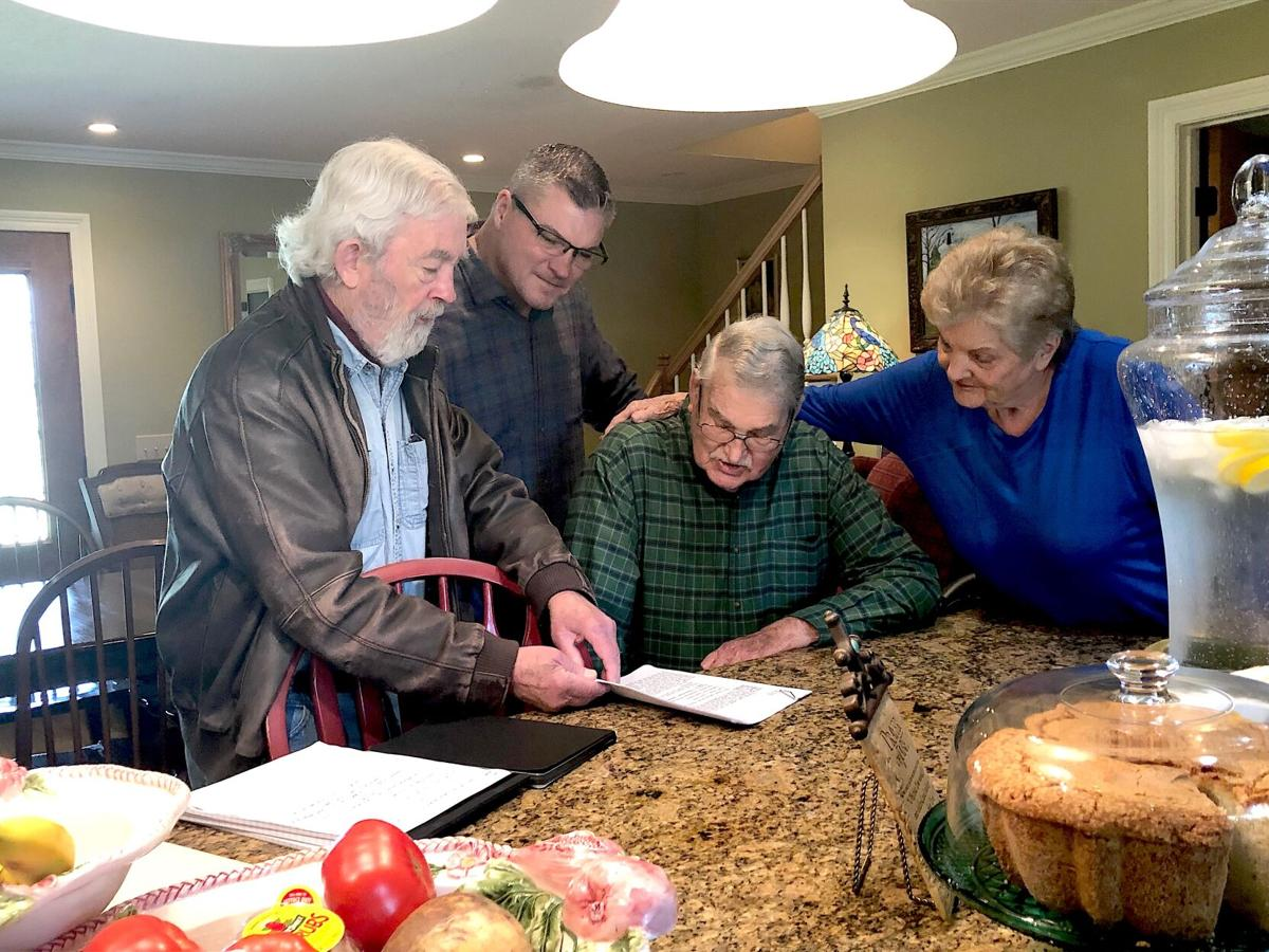 6.12 Landrum, Author Curtis Wilkie, left, with Tom Landrum seated beside him, wife Anne Landrum and Mike Landrum looking over FBI records. (Photo submitted).jpeg
