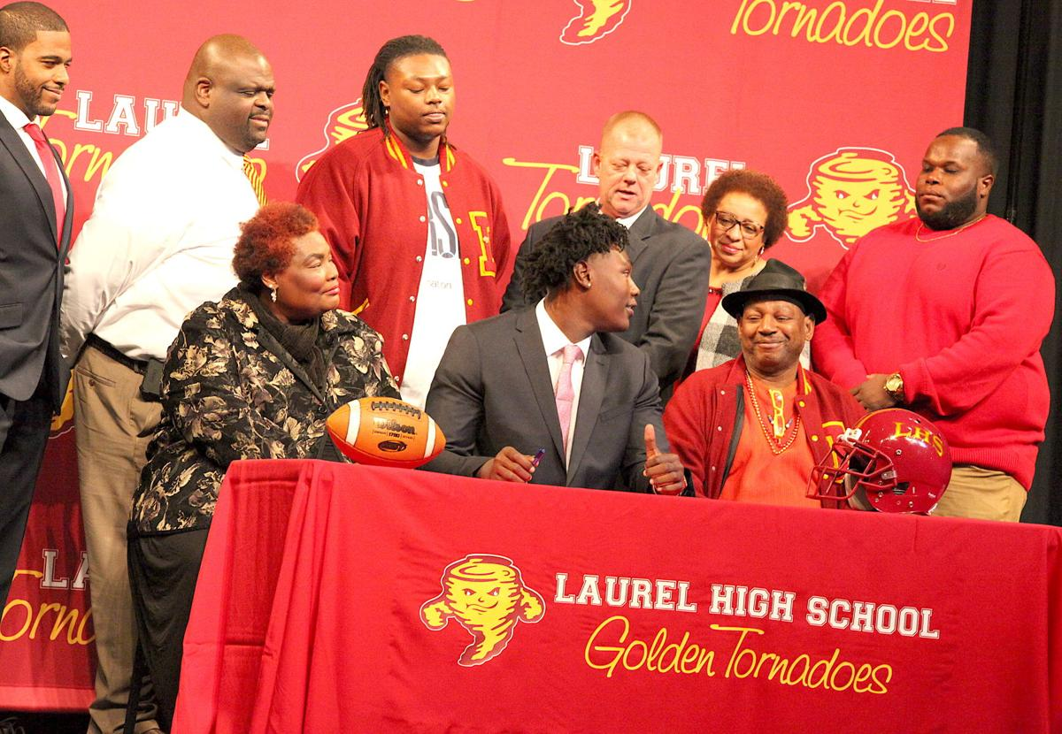 Laurel High School football standout Charles Cross gives a thumbs up to his father after sign- ing with Mississippi State. Seated with him are his mother Owedia Cross and father Mitchell Cross Sr. Standing, from left, are Principal Dr. Michael Eubanks, Assistant Principal Dr. Jaymar Jackson, brother Mitchell Cross Jr., head football coach Todd Breland, Assistant Principal Jeannine Agee and offensive line coach William Clay. (Photo by Mark Thornton)