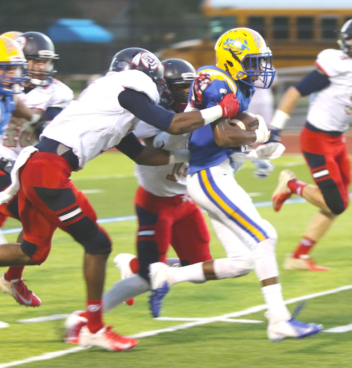 Bay High running back Max-well Lewis, right, is taken down by a pair of Braves. (Photo by Tyler Owen)