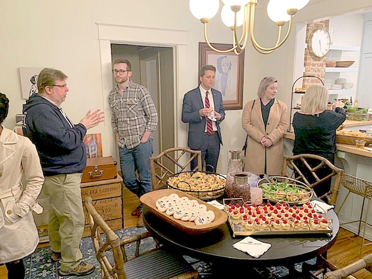 Keri Rowell's father Rodney, left, and others gather in the kitchen during the open house. (Photo by Tori Ellis).jpg