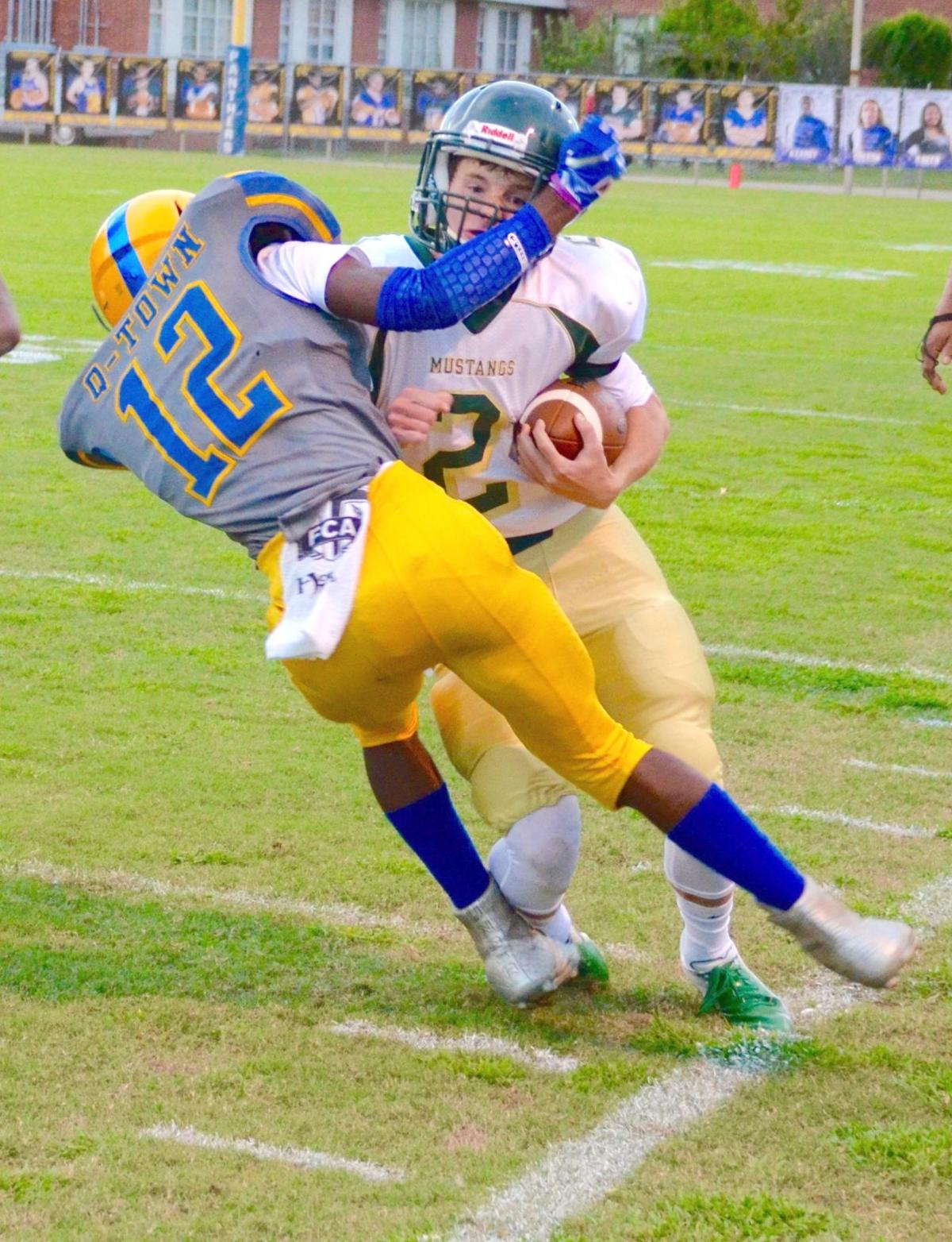 West Jones quarter- back Alan Follis (2) collides with a Quitman defender during the Mustangs' win on Fri- day night. (Photo by Guru Nichols)