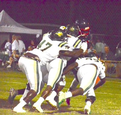 West Jones de- fensive linemen drag down a Forest Hill run- ning back for a safety during a 21-0 West Jones' victory on Friday. (Photo by Guru Nichols)