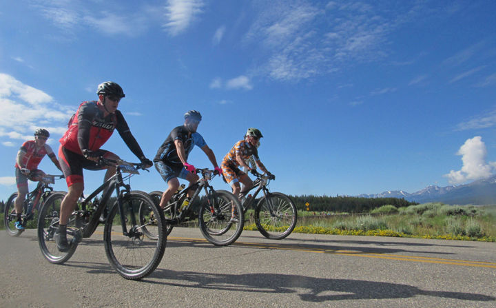 A group of cyclists races toward Turquoise Lake