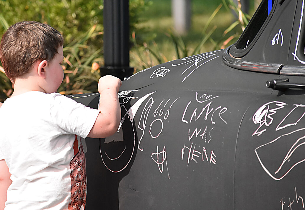 Child drawing on car