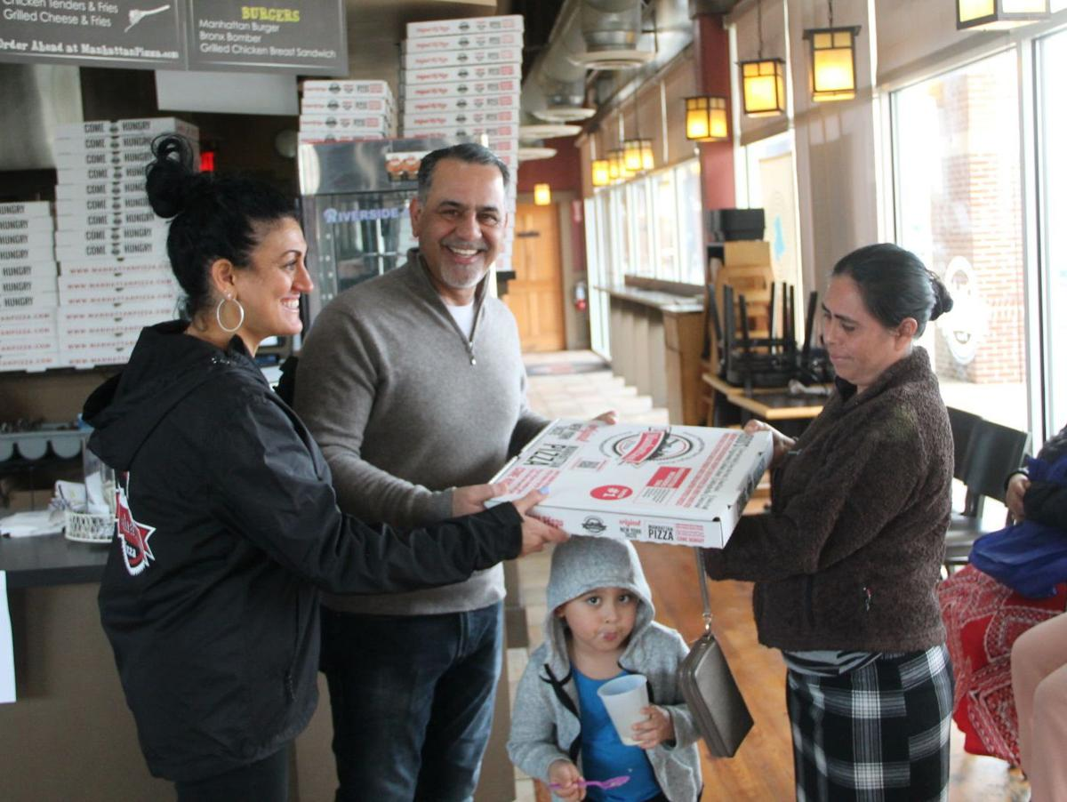 Manhattan Pizza donates pizza, produce and paper to community members in need