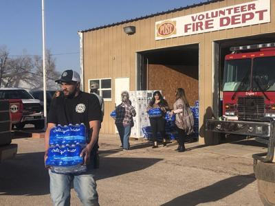 Volunteers hand out water bottles to residents in Post