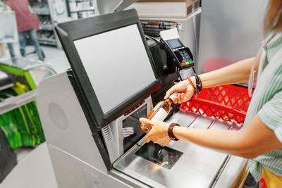 Woman scans bottle of wine at grocery self-service checkout