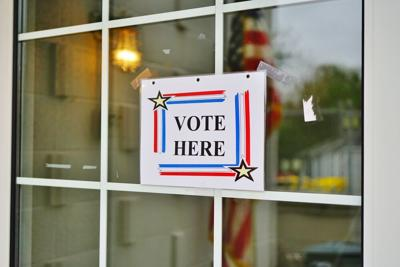 Vote here sign on glass window