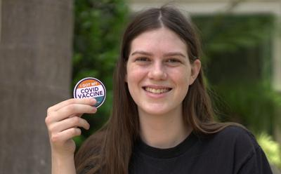 16-year-old girl holds up COVID-19 vaccine sticker