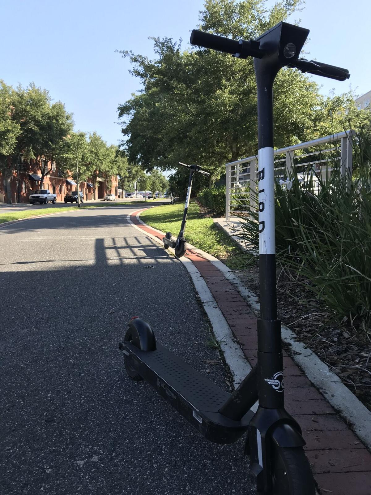 Two scooters parked on sidewalk