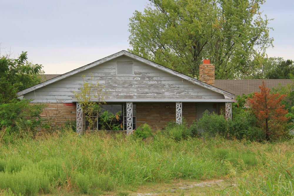 Old house overgrown with grass