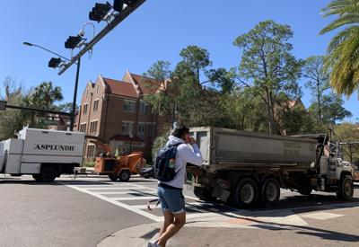 Pedestrian walking in front of trucks along West University