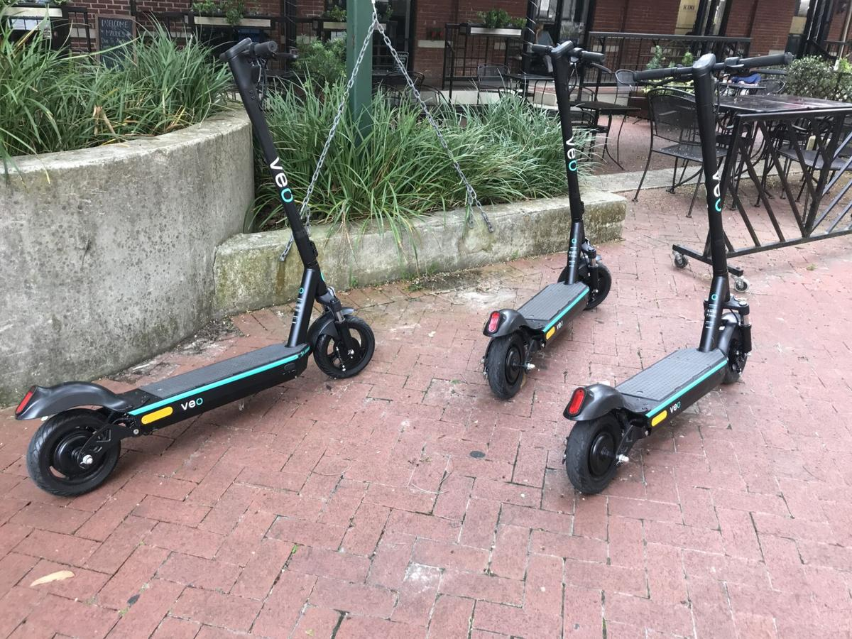 Three parked scooters on red brick sidewalk