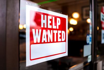 Red and white help wanted sign on storefront door