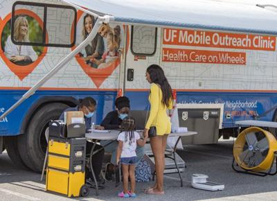 Mobile Outreach Clinic workers check in visitors