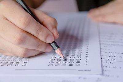 Student holding pencil taking school test