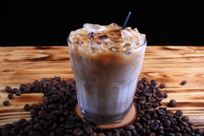 Iced coffee on wooden table with coffee beans