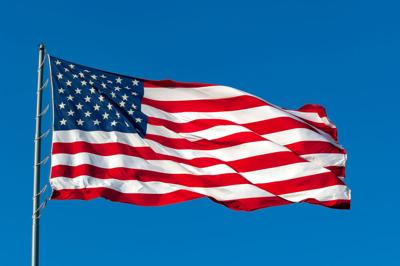 American flag waving in breeze with clear blue sky