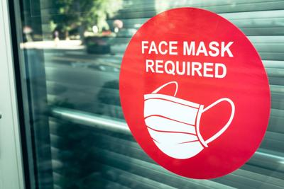 Red face mask required sign on glass door