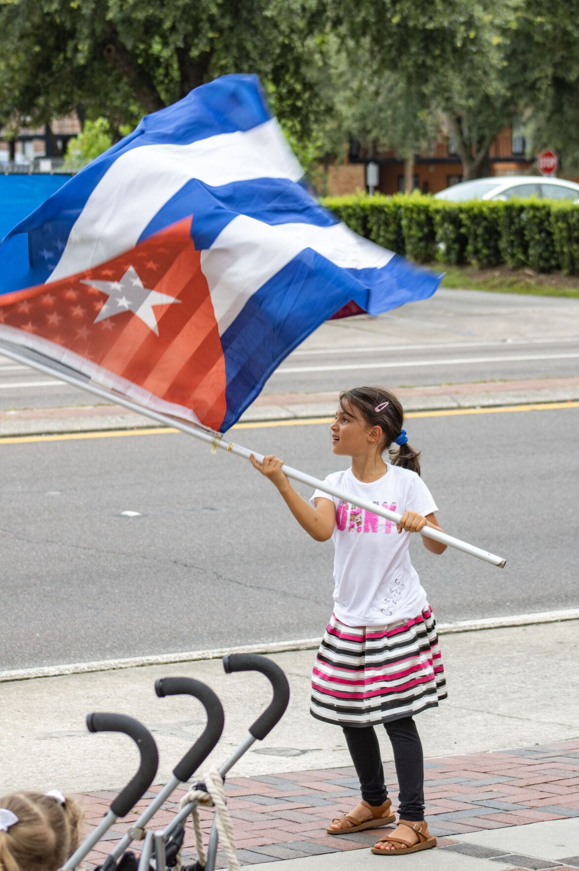 Girl waves Cuban flag at Gainesville rally