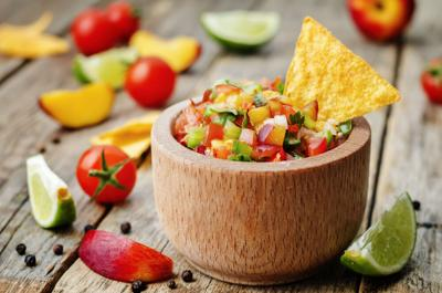 Peach salsa with chip on wooden table