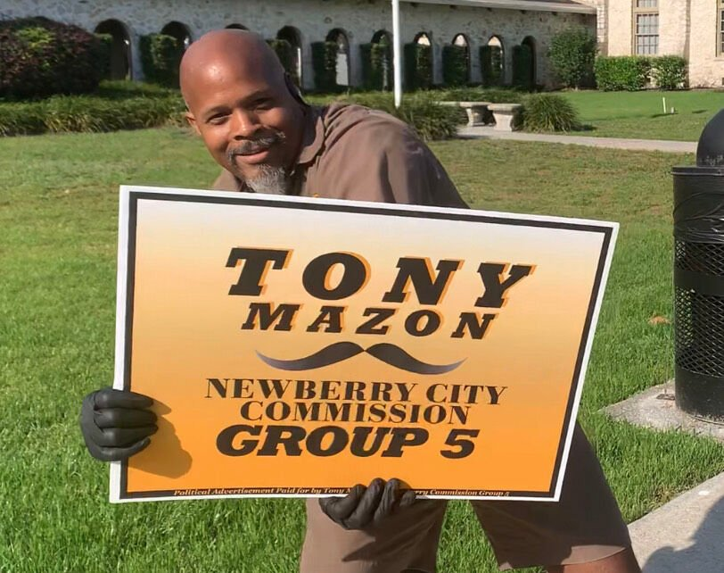 Tony Mazon holding sign and smiling
