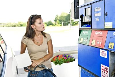 Woman filling vehicle with gas