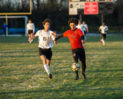 Overton's Jason Cartagena (11) holds off a Rossview defender as he heads up field with the ball