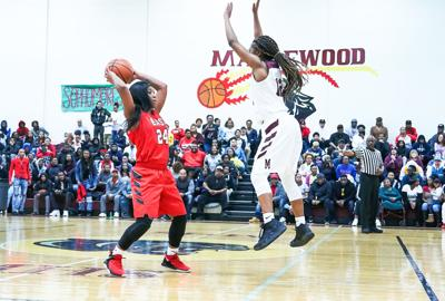 East Nashville's Jaelynn Knox looks to pass to a teammate as she's defended by Maplewood's Renata Watson at mid-court.