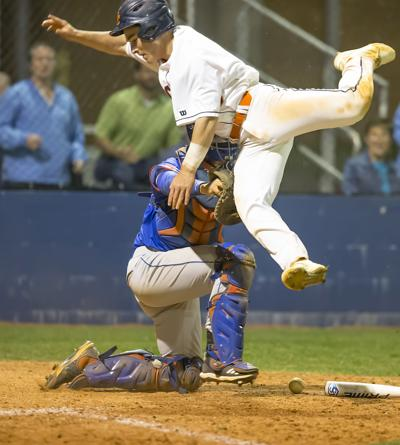 Dickson County's Clinton Shrader goes up in the air to avoid the Page catcher to score the winning run in the bottom of the seventh inning. Howard Abell / Mid Tenn Sports