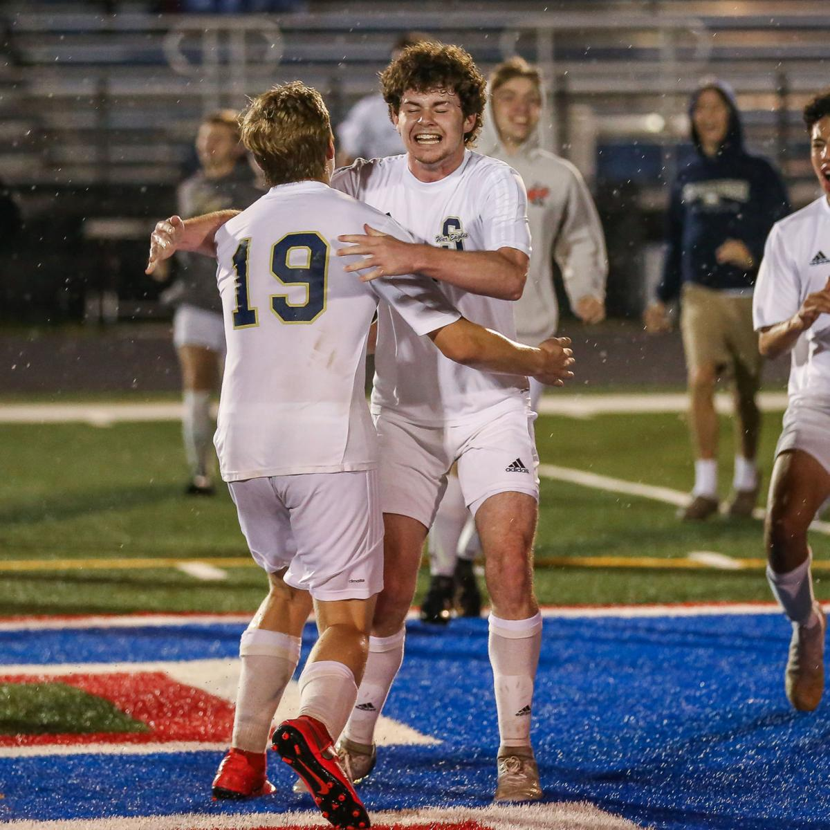 Hayden Roth (right) and Ethan Ivy celebrate Sycamore's first district boys soccer championship since 2005. JOSEPH SUMMERS