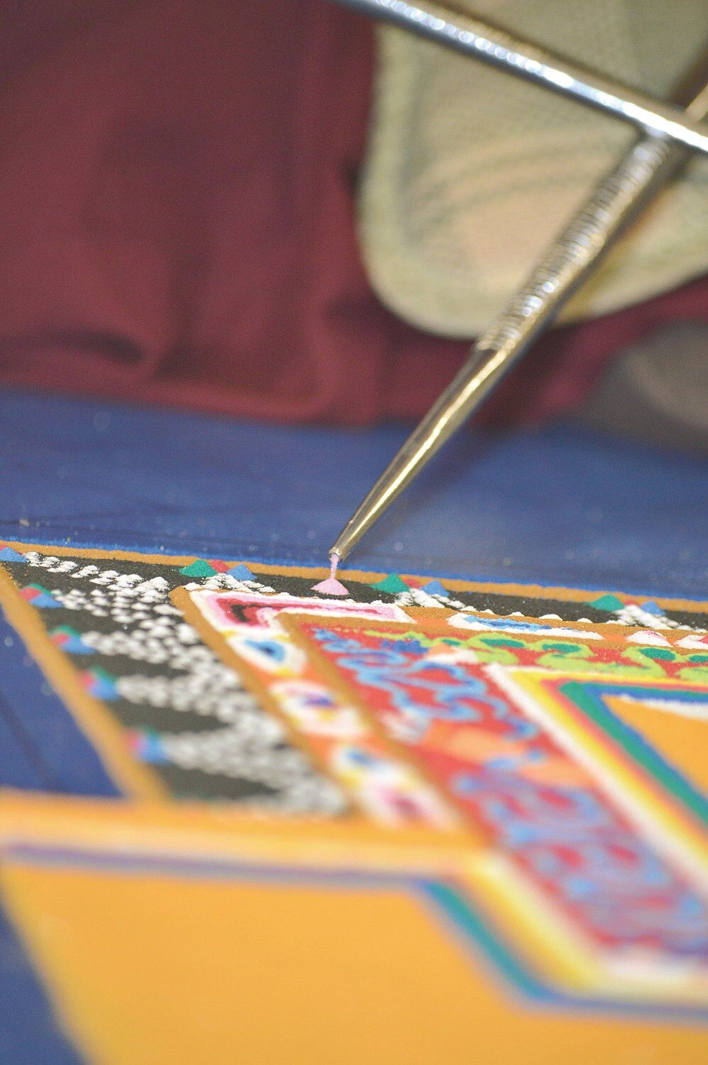 Tibetan monks creating mandala of compassion