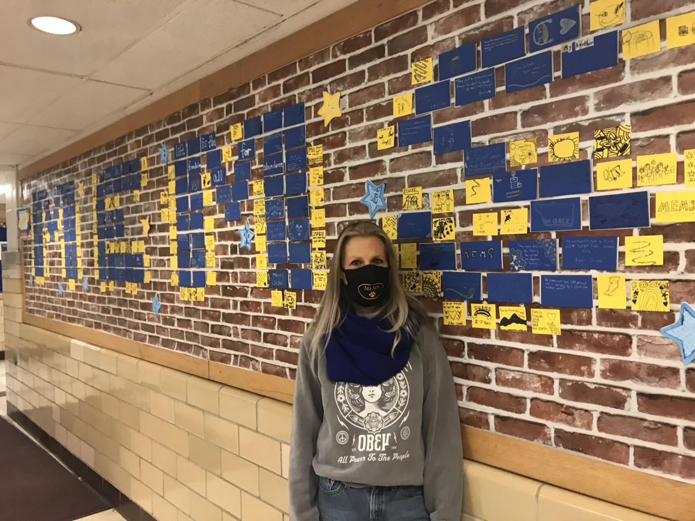 MEMS Art Instructor, Jen Tallini, stands next to the Wall of Gratitude .jpg