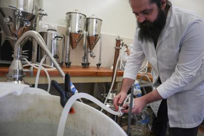CEO Nicolas Cetraro checks on the fermentation process of the hand sanitizer