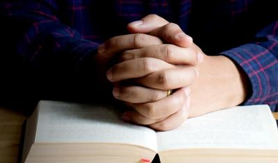 Hands of praying young man and Bible on a wooden table.