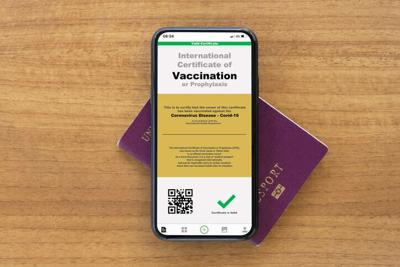 A smart phone with a digital illustration of an example of a certificate of vaccination against the Covid-19 disease is arranged on a passport. Travel concept during the Covid-19 pandemic.