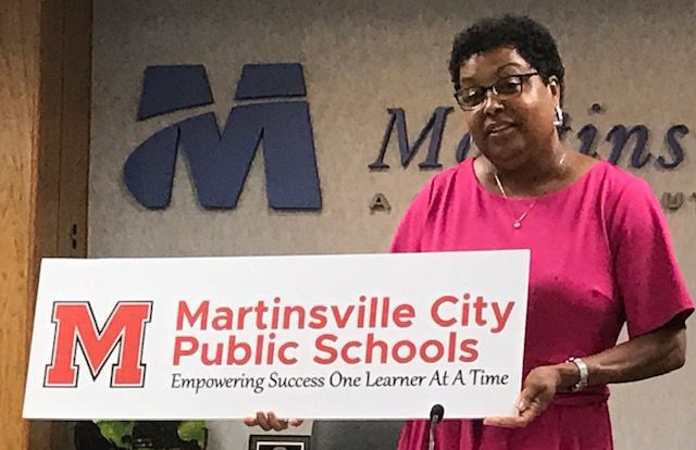 Donna Dillard with school division's new logo