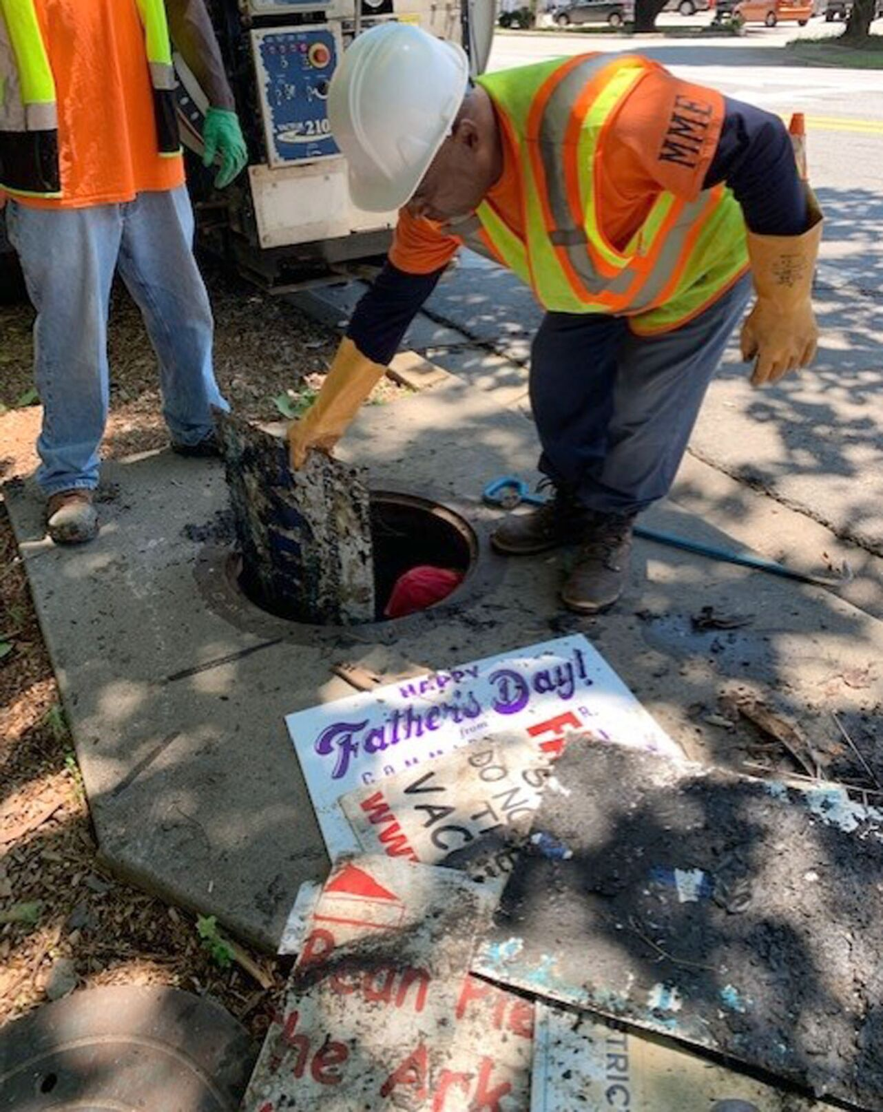 070721_MNS_SFulton_signs_002 worker pulls yard sign from drain