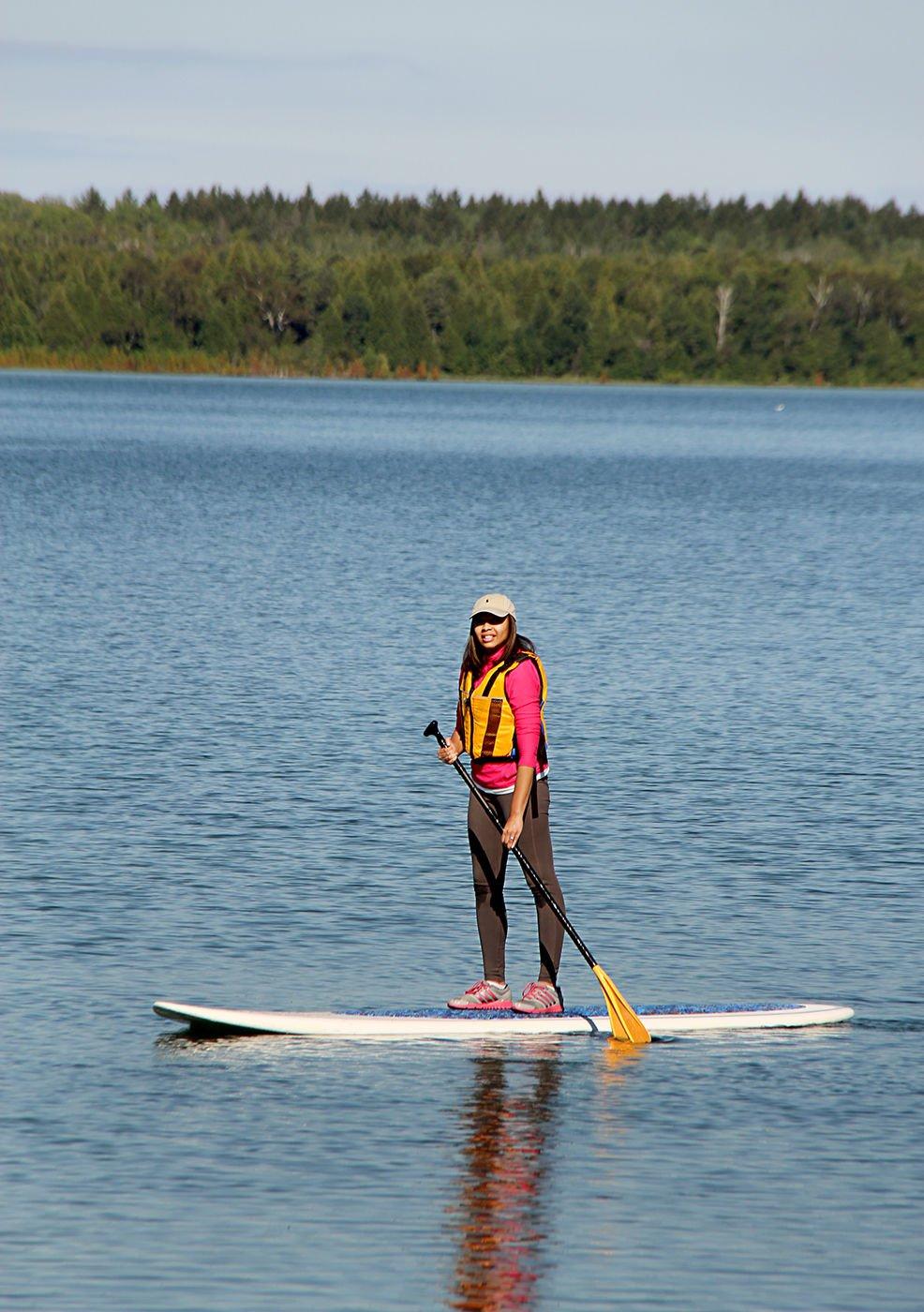 Writer Nicole Price stand-up paddleboarding in Wisconsin. (Photo / Jon Jarosh)
