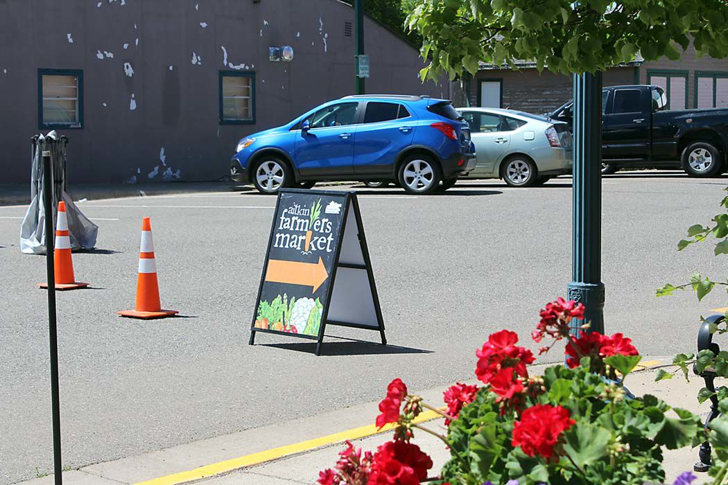 Brightly colored signs and flowers help visitors find the market's downtown location.