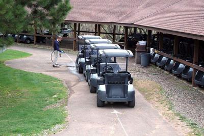 Joe Fremling hoses down used golf carts.