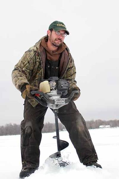 Tom Towle drills a hole in the ice a half-mile out from the eastern shore of Mille Lacs Lake.