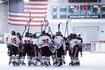 Members of the Northern Lakes Lightning hockey team celebrate March 18