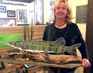 Kathryn Schreiber with a stained glass muskie she made.