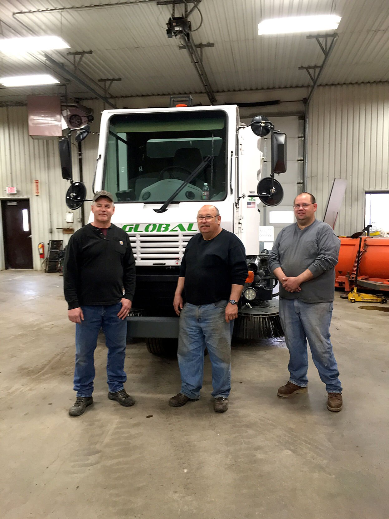The Aitkin Street Department crew in 2017 – Greg Handt, Bob Nicko  and Lon Nicko – with the new street sweeper.