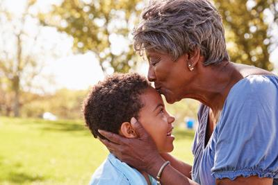 Close Up Of Grandmother Kissing Grandson In Park