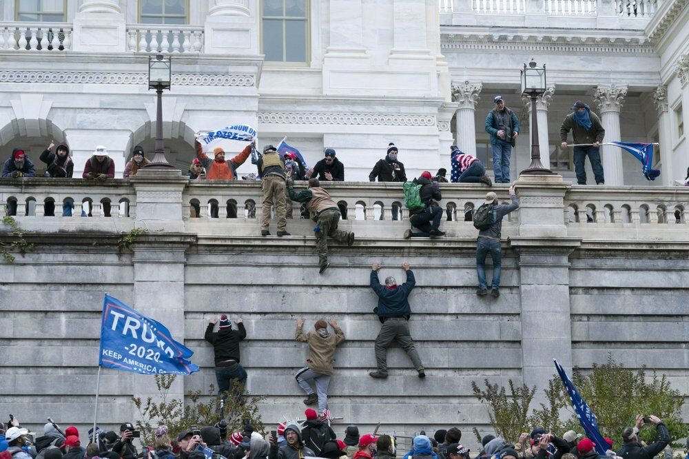 Supporters of President Donald Trump climb the west wall of the the U.S. Capitol