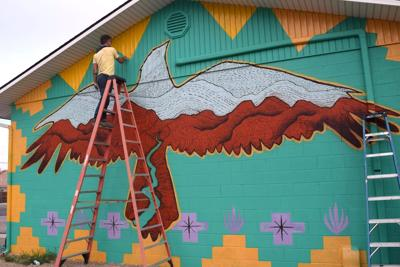 Jeremy Collins puts final touches on the red tail hawk: exterior of The Gym on 5th