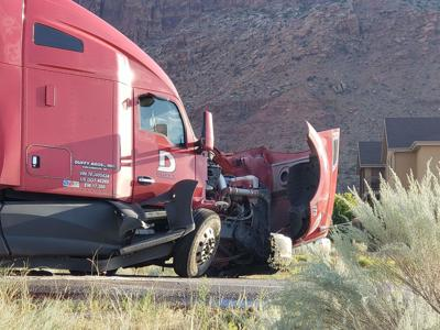 A semi-truck involved in a head-on collision sits at the side of Highway 191